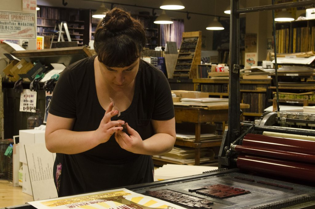 "Amber Richards, a graphic designer working a press at Hatch Printing Press. ""I love the hands-on aspect,"" she says. (Photo by: Nikita Sampath)"